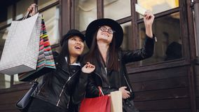 Excited female friends beautiful girls are taking selfie with smartphone and holding paper bags with purchases on autumn stock footage