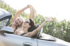 Excited female friends enjoying road trip in convertible on sunny day stock image