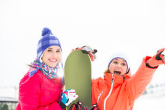 Excited female friends with snowboard outdoors Royalty Free Stock Photo