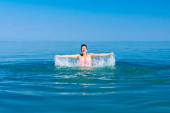 Excited female jumping with widespread hands in shallow sea water. Restless beautiful cheerfully woman is having fun and jumping out with widespread hands in sea royalty free stock photography