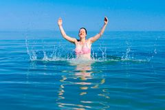Excited female jumping with widespread hands in shallow sea water. Restless beautiful cheerfully woman is having fun and jumping out with widespread hands in sea stock photo