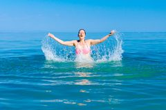 Excited female jumping with widespread hands in shallow sea water. Restless beautiful cheerfully woman is having fun and jumping out with widespread hands in sea stock photography