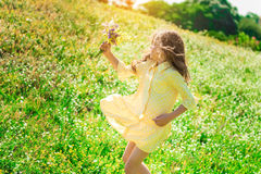 Excited female kid playing on meadow with flowers royalty free stock photos