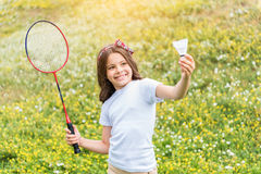 Excited female kid playing tennis on field stock photos