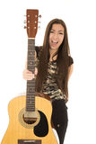 Excited female model holding out her acoustic guitar Stock Photo