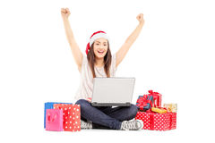 Excited female with santa hat working on laptop and gifts around Royalty Free Stock Photography