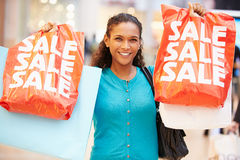Excited Female Shopper With Sale Bags In Mall. Close Up Image Of Excited Female Shopper With Sale Bags In Mall Smiling stock photography