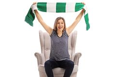 Excited female sports fan sitting in an armchair and cheering with a scarf royalty free stock image