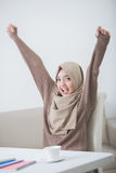Excited female student with hijab raise her arm up while studyin. Portrait of excited female student with hijab raise her arm while studying Royalty Free Stock Images