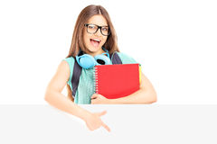 Excited female student holding notebooks and pointing on a panel. Excited female student holding notebooks and pointing on a blank panel isolated on white Royalty Free Stock Image