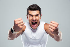 Excited fitness man. Shouting at camera over gray background royalty free stock photography