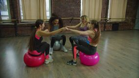 Excited fitness women bouncing on exercise balls