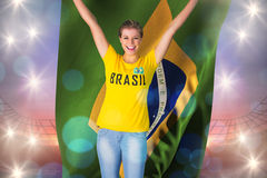 Excited football fan in brasil tshirt holding brasil flag Stock Photos