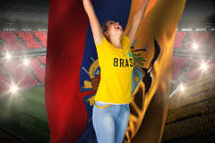 Excited football fan in brasil tshirt holding ecuador flag Royalty Free Stock Photography