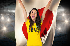 Excited football fan in brasil tshirt holding japan flag Stock Image