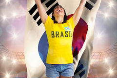 Excited football fan in brasil tshirt holding south korea flag. Against large football stadium under bright blue sky stock photography
