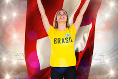 Excited football fan in brasil tshirt holding swiss flag Royalty Free Stock Images