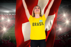 Excited football fan in brasil tshirt holding swiss flag Royalty Free Stock Photo