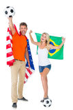 Excited football fan couple holding usa and brazils flag Royalty Free Stock Photography