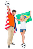Excited football fan couple holding usa and brazils flag Royalty Free Stock Images