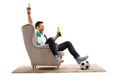 Excited football fan with a scarf and a beer bottle seated in an Stock Photos