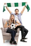 Excited football fans sitting in an armchair and cheering Stock Images