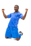 Excited football player in blue cheering on his knees Royalty Free Stock Image