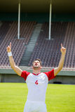 Excited football player with hands raised Stock Photography