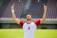Excited football player with hands raised Royalty Free Stock Photo