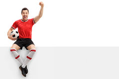 Excited football player sitting on a panel and gesturing happine Royalty Free Stock Images