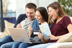 Excited friends buying trip on line. Three excited friends buying a trip on line with a credit card and a laptop sitting on a couch in the living room at home Royalty Free Stock Images