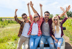 Excited friends on car outdoor countryside raise arms people smile holding hands up Royalty Free Stock Photo