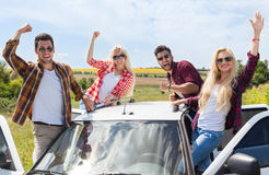 Excited friends on car roof outdoor countryside raise arms people smile Stock Image
