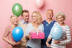 Excited friends congratulating mature lady with birthday stock image