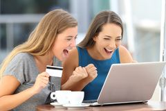 Excited friends discovering offer buying on line. Two excited friends discovering offers buying on line with a laptop and a credit card sitting in a bar terrace Stock Images