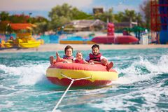 Excited friends, family having fun, riding on water tube during Stock Photo
