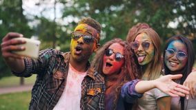 Excited friends girls and guys are taking selfie with colored faces and hair using smartphone, stylish young man is