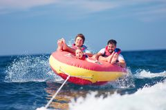 Excited friends, family having fun, riding on water tube during summer vacation Stock Image