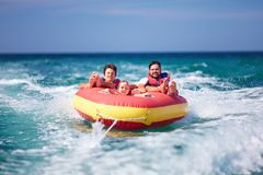 Excited friends, family having fun, riding on water tube during summer vacation Stock Photography