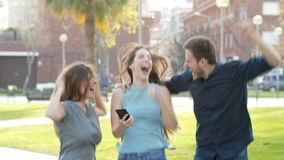 Excited friends jumping after checking phone content. Excited friends jumping in the street after checking smart phone content stock footage