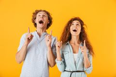 Excited friends loving couple pointing. Image of excited friends loving couple standing over yellow background pointing royalty free stock image
