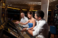 Excited friends playing at gaming machines royalty free stock images