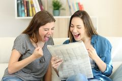 Excited friends reading newspaper news. Sitting on a couch in the living room at home Royalty Free Stock Photo