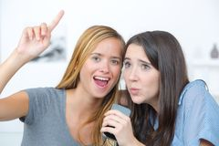 Excited friends singing on couch at home Stock Images