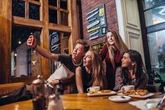 Excited friends taking selfie with smartphone sitting at table having night out. Excited friends taking selfie with smartphone sitting at table having night out Royalty Free Stock Image