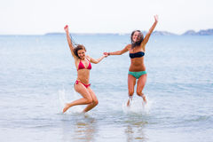Excited friends. Excited young women jumping in the seawater of the Mediterranean sea Royalty Free Stock Photo