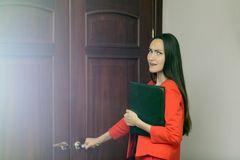 Excited and frightened woman in a red suit with documents in hand knocking at the door to the boss Stock Photo