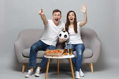 Excited fun couple woman man football fans in white t-shirt cheer up support favorite team with soccer ball, rising. Excited fun couple women men football fans royalty free stock photos