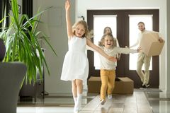 Excited funny kids running inside new house on moving day. Excited funny kids boy and girl running inside luxury big modern house on moving day, cute children stock images