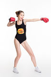 Excited funny young woman in boxing gloves making direct hit Royalty Free Stock Photography